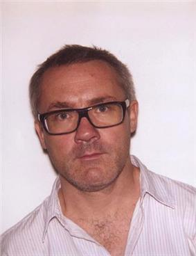 Damien Hirst, a man wearing glasses with brown rims, and a white shirt with faint vertical stripes