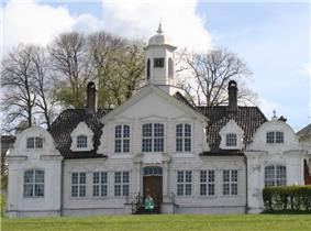 Ornate, symmetrical, wooden house with two smaller wings with decorative engaged columns. The pitched roof has gables. The windows are paned and the front door has columns on either side.
