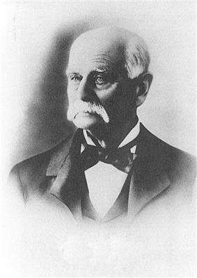 Head shot of an older man with white hair and moustache, dressed in tuxedo and bow tie.