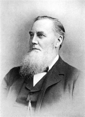 Man with short receding hair and beard, dressed in Victorian clothing