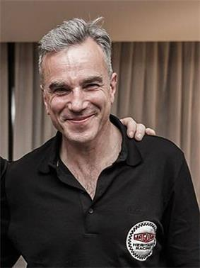 A smiling man with grey hair wearing a black collared shirt.