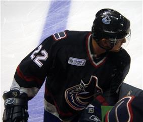 An ice hockey player leaning over on his bench with his head turned to the right. He wears a dark blue jersey and a visored helmet.