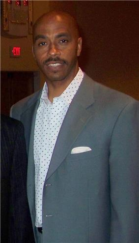 A man, wearing a gray suit and white shirt, is standing and posing for a photo.