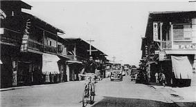 Man bicycling down street in old photo, with cars in background