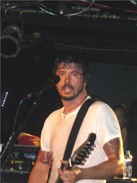 A bearded man wearing a white shirt plays guitar in front of a microphone.