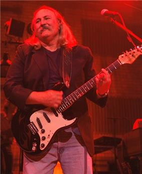 A man with a mustache and shoulder-length hair wearing jeans and holding a guitar, standing behind a microphone.