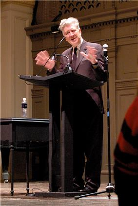 A man standing at a lectern, delivering a speech
