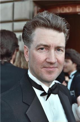 A man in a tuxedo looks directly at the camera, slightly smiling.