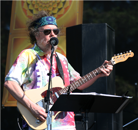 David Nelson onstage at an outdoor concert, playing an electric guitar