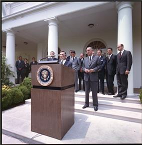 In this photo, David Rockefeller takes the podium as President Lyndon Johnson looks on in the White House Rose Garden on June 15, 1964 to announce the launch of the International Executive Service Corps.