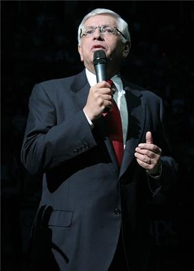 A man in his 50s with white hair speaks into a microphone. He wears a gray suit, red tie, and glasses.