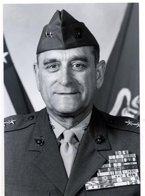 Head and shoulders of a middle-aged white man with a subdued smile wearing a garrison cap with two stars on either side and a military jacket with a large array of ribbon bars covering the entire left breast.