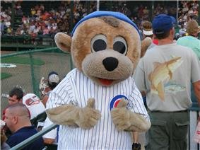 A color photograph of a person wearing an anthropomorphized grizzly bear costume and dressed in a white pinstriped baseball uniform with a red, white, and blue patch on the chest reading,