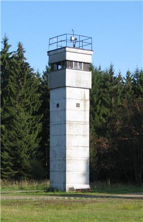 A square greyish tower on a meadow, with trees in the background. Only the topmost section has windows; there is a searchlight on the tower's flat roof, and a railing around the roof's outer edge.