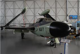 A green and black de Havilland Sea Venom jet-powered aircraft with wings folded up and
