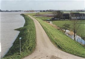 A river dike with a narrow road on top, high water levels on the river to the left, low lying meadows and a farm on the right