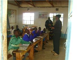 Smiling teacher standing in front of eight older boys in Africa