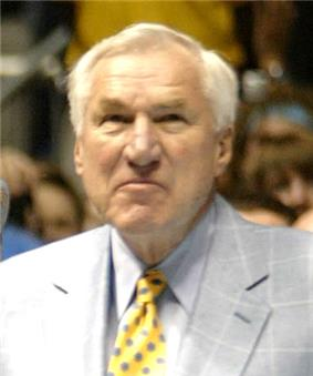 A man wearing a grey jacket and a yellow tie with blue polka dots