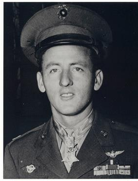 Head and shoulders of a young white man with a peaked cap pushed high up on his forehead, wearing a military jacket with two rows of ribbon bars on the left breast and a star-shaped medal hanging from a ribbon around his neck.