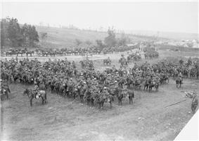 A large group of men and horses drawn up into lines in a field and on the adjoining road. A hill with trees and tents can be seen in the background.
