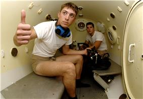 Photograph of the cramped interior of a cylinder containing two benches and two diver trainees