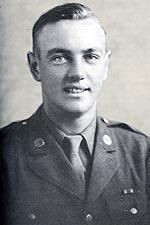 Head and shoulders of a young white man with neatly combed hair wearing a military jacket with a round pin on each lapel over a shirt and tie.