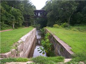 A narrow stone-lined canal lock filled with water surrounded by grass. In the background a path follows the canal at left and a modern bridge crosses it.
