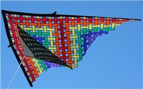A colorful triangular kite against a blue sky