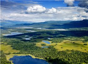 Aerial photograph of several lakes, interspersed with conifer forests and meadows, with tall mountains in the distance and clouds and blue sky overhead. The clouds are casting shadows over the forests and lakes.