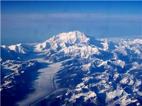 In an aerial image, a mountain is surrounded by many smaller mountains and a glacier
