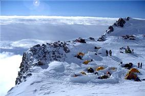 Several tents are pitched near the edge of a snow-covered cliff