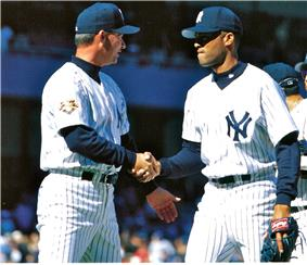 Rivera shakes Gary Denbo's hand wearing a white pinstriped baseball uniform with navy cap and undershirt.