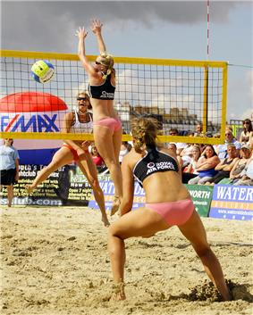 Female figures on sand. Two are on the nearside of a net and one on the far side. Two are jumping. To the right are an audience.