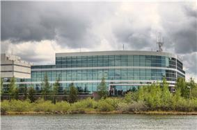 A modern three-storey office building with reflective greenish glass windows underneath a cloudy sky along the lakeshore, seen from the opposite side