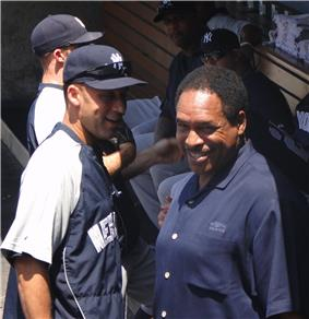 Derek Jeter and Dave Winfield standing together in a dugout.