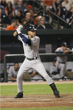 A man in a grey baseball uniform with a navy helmet prepares to swing at a pitch