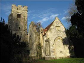 To the left is a battlemented tower, in the middle a ruined wall, and to the right the end of a stone chapel with a red tiled roof