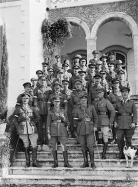 Soldiers in cavalry uniform on steps outdoors, with canine mascot