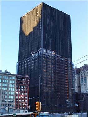 Ground-level view of a 40-story building; the highest 20 floors have a black tarp-like covering. The exterior facade has been removed from the lower 20 floors, leaving exposed steel columns visible.