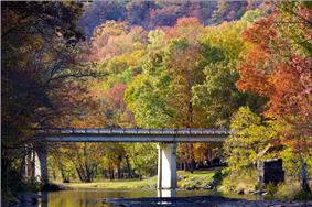 Red, green and orange fall foliage surrounds a small bridge spanning a quiet, rocky Lee Creek