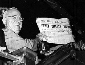 Man in gray suit and wire glasses holding newspaper that says