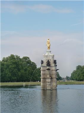a golden female statue on top of a white marble column, smaller black statues adorn the column and there is a water jet into a surrounding pool. In the background are trees