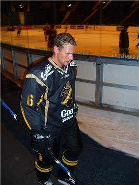 An ice hockey walking to the right of the camera. Behind is the ice hockey rink. He has short brown hair and is not wearing a helmet. He is wearing a black uniform.