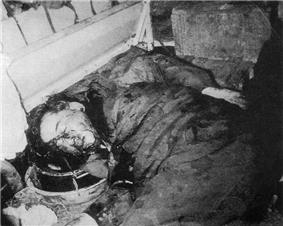 Middle-aged black-haired man lies face half-down on the floor, covered on his face and dark suit and trousers with blood. His hands are behind his back.