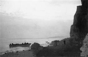 ship beaching with men disembarking, on the right is a cliff face