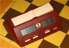 Photo shows a digital chess clock. There are two clocks, one on each side and a button on top of each stops that clock and starts the other