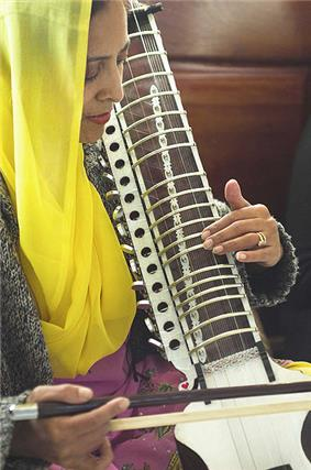 Woman in yellow scarf bowing an instrument