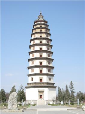 An eleven story octagonal pagoda crowned with a large bronze and iron spire. Each floor has a carved stone eave that serves as a functional, all be it small, balcony. The building is painted white.