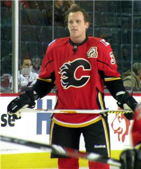 A Calgary Flames player observes his teammates who are off camera.  On his uniform is a small patch that uses Atlanta's