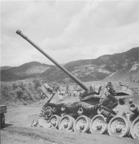 A damaged main battle tank, lying to one side of the road with its main gun traversed and its tracks blown off